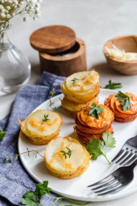 Sweet Potato Stacks and Yukon Gold Potato Stacks on white plate with parsley garnish and white flowers background with blue napkin