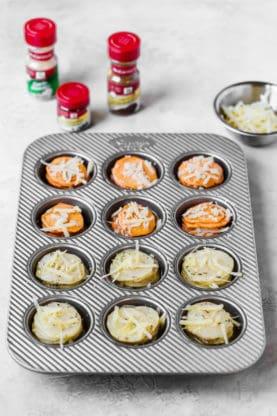 Sweet Potato and Yukon Gold potato slices in silver muffin pan preparing to bake