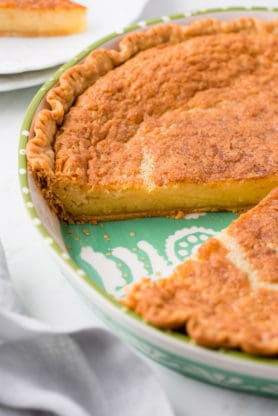 Close up of missing slice from vanilla buttermilk pie recipe on green pie plate