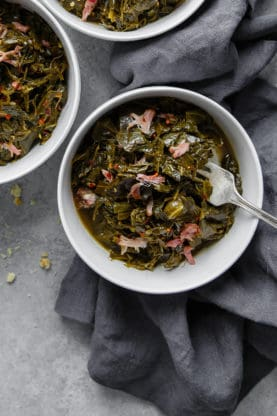 Bowls of braised collard greens with ham hock in gray bowls over gray background