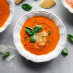 Tomato Soup in white bowl garnished with fresh basil, oil and shredded parmesan cheese