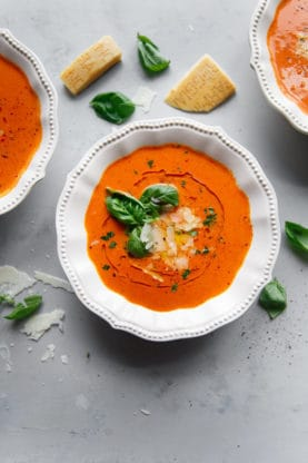Homemade Tomato Basil Soup recipe in white bowl garnished with fresh basil, oil and shredded parmesan cheese with three bowls of soup