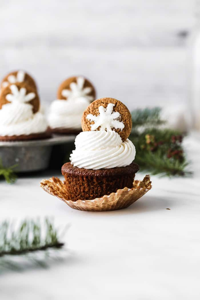Perfect Gingerbread Cupcakes scattered against a white background with delicious buttercream piped high on each one