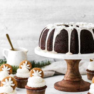 Gingerbread cupcakes and gingerbread pound cake on cake stand against white background with greenery