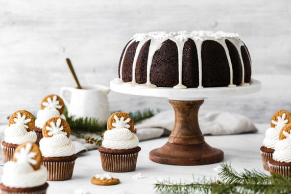 Gingerbread cake on cake stand with gingerbread cupcakes surrounding it on white background