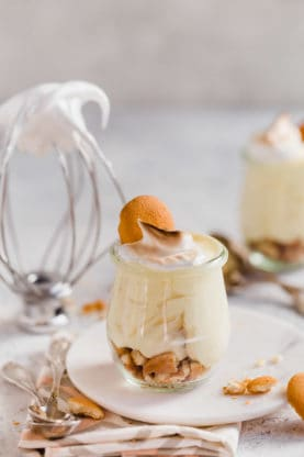 Straight on shot of homemade banana pudding in mini glasses with nilla cookies and meringue