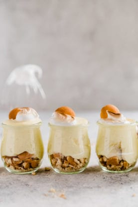 Three homemade old fashioned banana pudding in small miniature glasses with wafer cookies. The best banana pudding recipe ever!