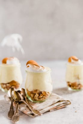 Three homemade old fashioned banana pudding in small miniature glasses with wafer cookies