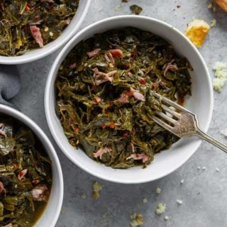 Overhead of three white bowls filled with Southern Collard Greens with hamhock against gray background