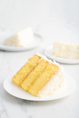 Close up of three slices of Pineapple Coconut Cake recipe on white plates