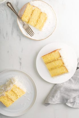 Overhead of three slices of Pineapple Coconut Cake on white plates