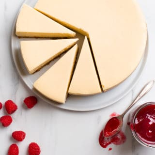 New York Cheesecake overhead shot with full cheesecake and four slices with raspberries and raspberry sauce