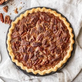 A whole Southern Pecan Pie in homemade butter crust with a bowl of pecans nearby against white background