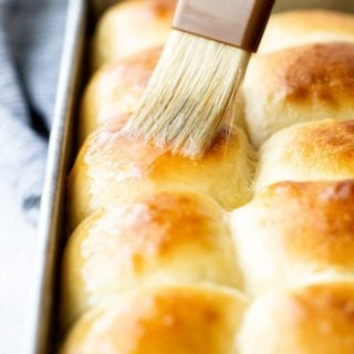 A close up of sweet rolls being brushed with melted butter