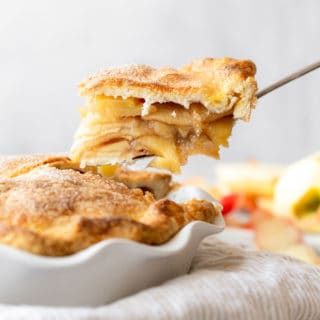 A slice of apple pie with apple filling being lifted from pie ready to serve