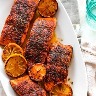 A delicious white platter filled with blackened salmon fillets with lemon wedges