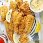 Perfectly fried catfish fillets with hot sauce, lemon wedges and tartar sauce