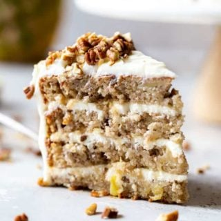 A lovely slice of a hummingbird cake recipe with pineapple cream cheese frosting and nuts ready to eat