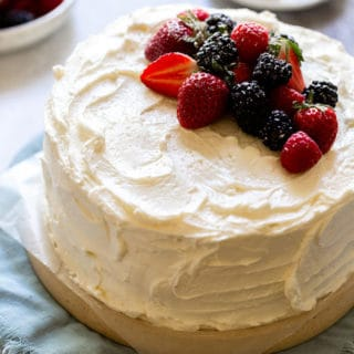 a devil's food cake frosted with swiss meringue buttercream and topped with fresh berries