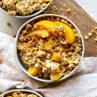 Delicious bowls of peach oatmeal with rolled oats and fresh peaches on table for breakfast