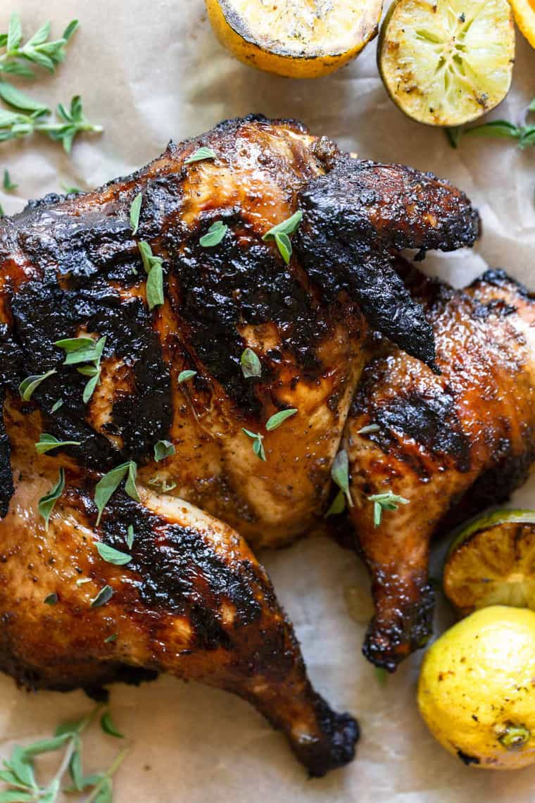 a delicious charred grilled spatchcock chicken sprinkled with herbs next to grilled citrus fruit