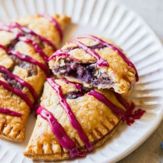 A close up of two blueberry hand pies with one split open showing cream blueberry filling on a white plate