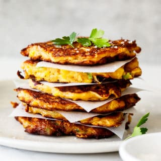 A beautiful stack of corn fritters with parchment paper in between topped with parsley