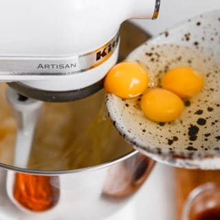 eggs being added to a stand mixer while baking