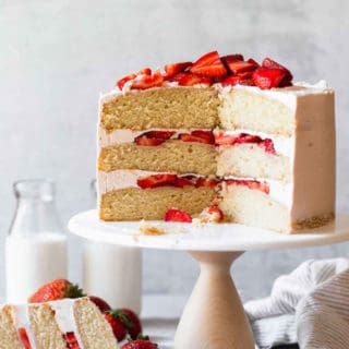 A vanilla cake with strawberry filling sliced with a large slice on a plate with strawberries near by