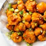 A pile of delicious golden fried cauliflower tossed in buffalo sauce and topped with green onions against white parchment paper