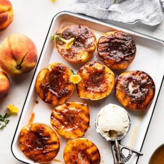 A white tray of brown sugar grilled peach halves with a scoop of vanilla ice cream next to fresh peaches
