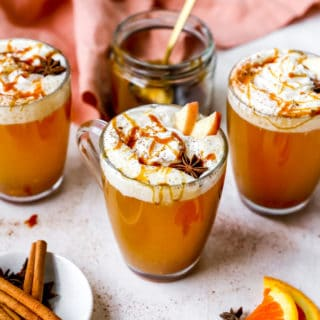 Three mugs of spiced cider with whipped cream and caramel sauce surrounded by a coral napkin