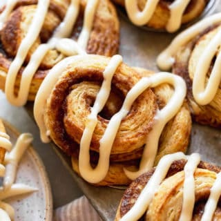 A close up of cinnamon roll biscuits in tin with a design of icin