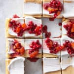 Delicious maple cheesecake cut in squares with red compote on top for serving