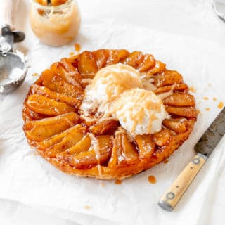 A classic french apple tarte ready to serve with ice cream and cream sauce against white background