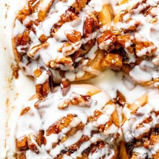 Pecan cinnamon rolls after being drizzled with a cream cheese icing in baking dish