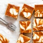 Swirled cheesecake bars with pumpkin scattered against parchment paper
