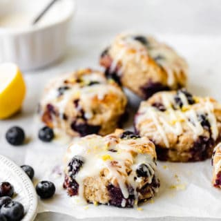 A stack of blueberry lemon drop biscuits piled high with scattered blueberries and lemon slices nearby