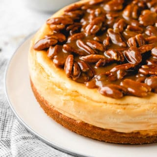 A close up of pecan cheesecake with a caramel topping on a white plate