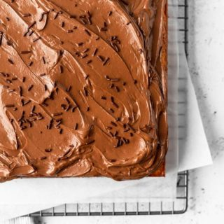 The corner of a sheet cake topped with chocolate swiss meringue buttercream and chocolate sprinkles