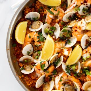 A close up of a completed skillet of seafood paella filled with mussels, shrimp and clams ready to serve