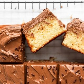 A sheet cake being spread with chocolate buttercream