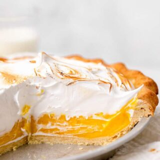 A close up of cut open lemon pie with torched meringue topping