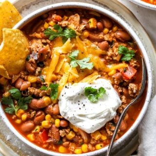 A close up of taco soup in large white bowl with cheese and sour cream with tortilla chips