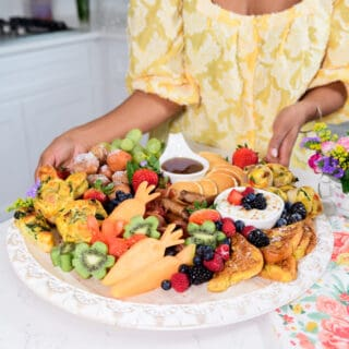 A close up of a brunch board to serve on a holiday with brown hands holding it up