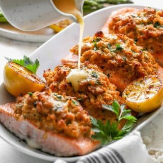 Crab stuffed salmon filets on a white platter with lemon sauce being poured on top