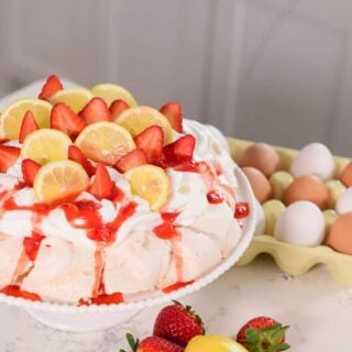 A delicious lemon strawberry pavlova ready to enjoy with lemons and strawberries surrounding it