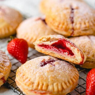 A close up of strawberry hand pies with one cut open showing strawberry filling