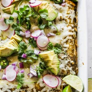 A close up of blackened chicken enchiladas with melty cheese, avocado and cilantro on top