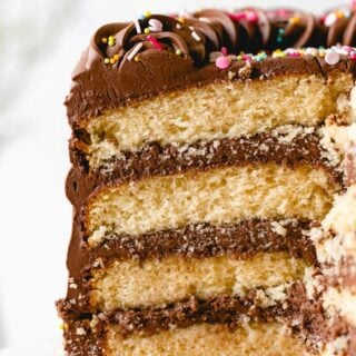 A close up of a sliced yellow birthday cake with sprinkles on top